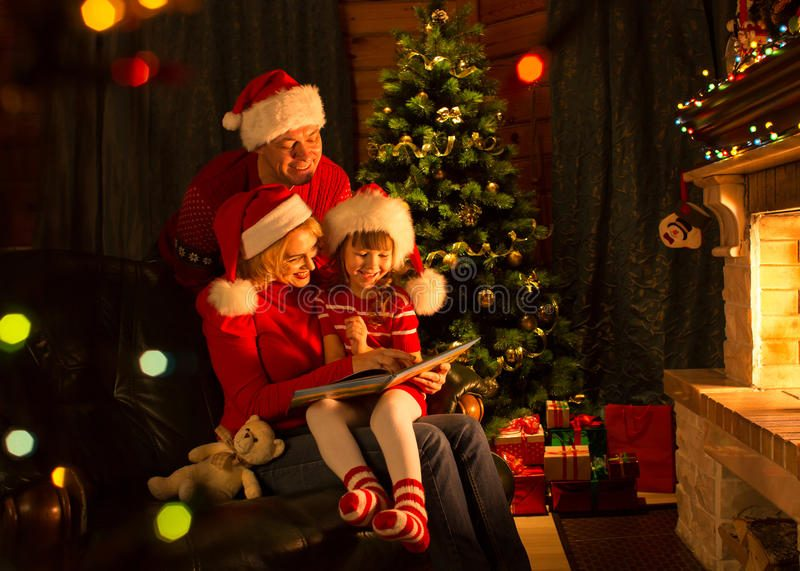 grandparents reading to child by christmas tree